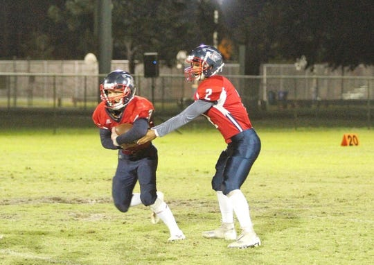 Master's Academy quarterback Jordan Girton hands off to running back Brandon Dampier during the Patriots' FCAPPS playoff game against St. Petersburg-Canterbury, Friday, Nov. 16, 2018, at Gifford Park.