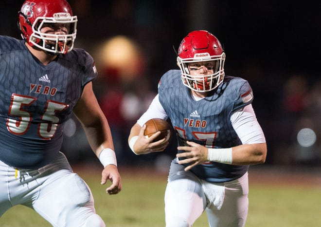 Vero Beach quarterback Nick Celidonio runs under pressure from Dr. Phillips (Orlando) defenders for a gain of a couple yards, with help from teammate John Moran (left), during the first quarter of the Class 8A Regional Semifinal high school football game Friday, Nov. 16, 2018, at the Citrus Bowl in Vero Beach.