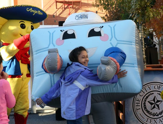 """Ava Glenn, 9, of El Paso reaches to hug an El Paso Electric mascot at the """"Break the Ice"""" party and news conference Friday at Downtown's Arts Festival Plaza as residents celebrated the opening of the third season of WinterFest."""