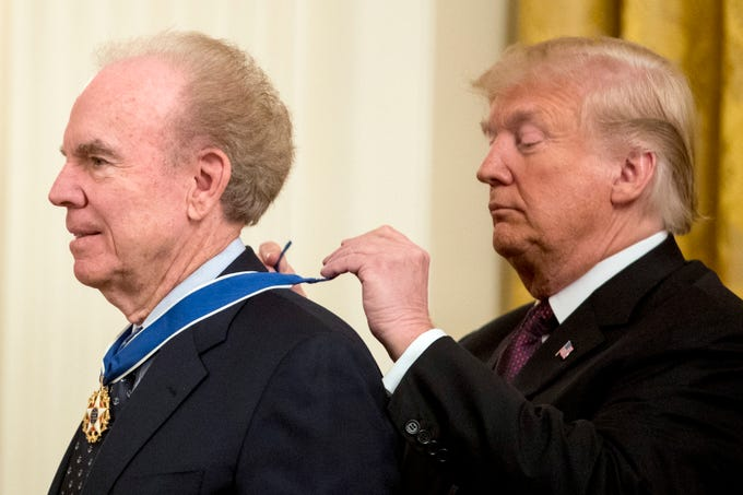 President Donald Trump awards former professional football player Roger Staubach the Medal of Freedom during a ceremony in the East Room of the White House in Washington, D.C., on Friday, Nov. 16, 2018.