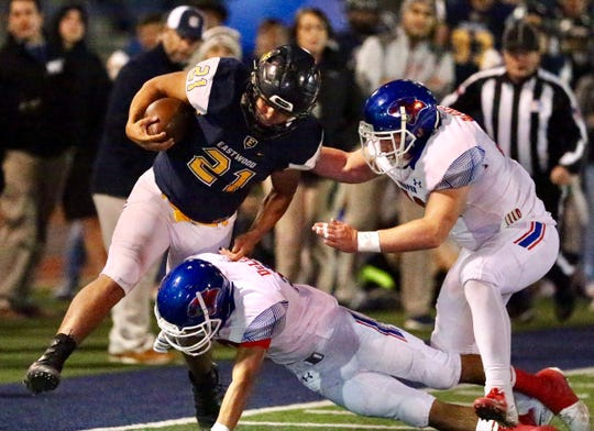 El Paso Eastwood running  back Noah Rios (21) gains yardage before being forced out of bounds by Cooper's Justin DeLeon, center, and another Cooper defender. Cooper won the Region I-5A Division I bi-district playoff game 49-41 on Friday, Nov. 16, 2018, at Trooper Field in El Paso.