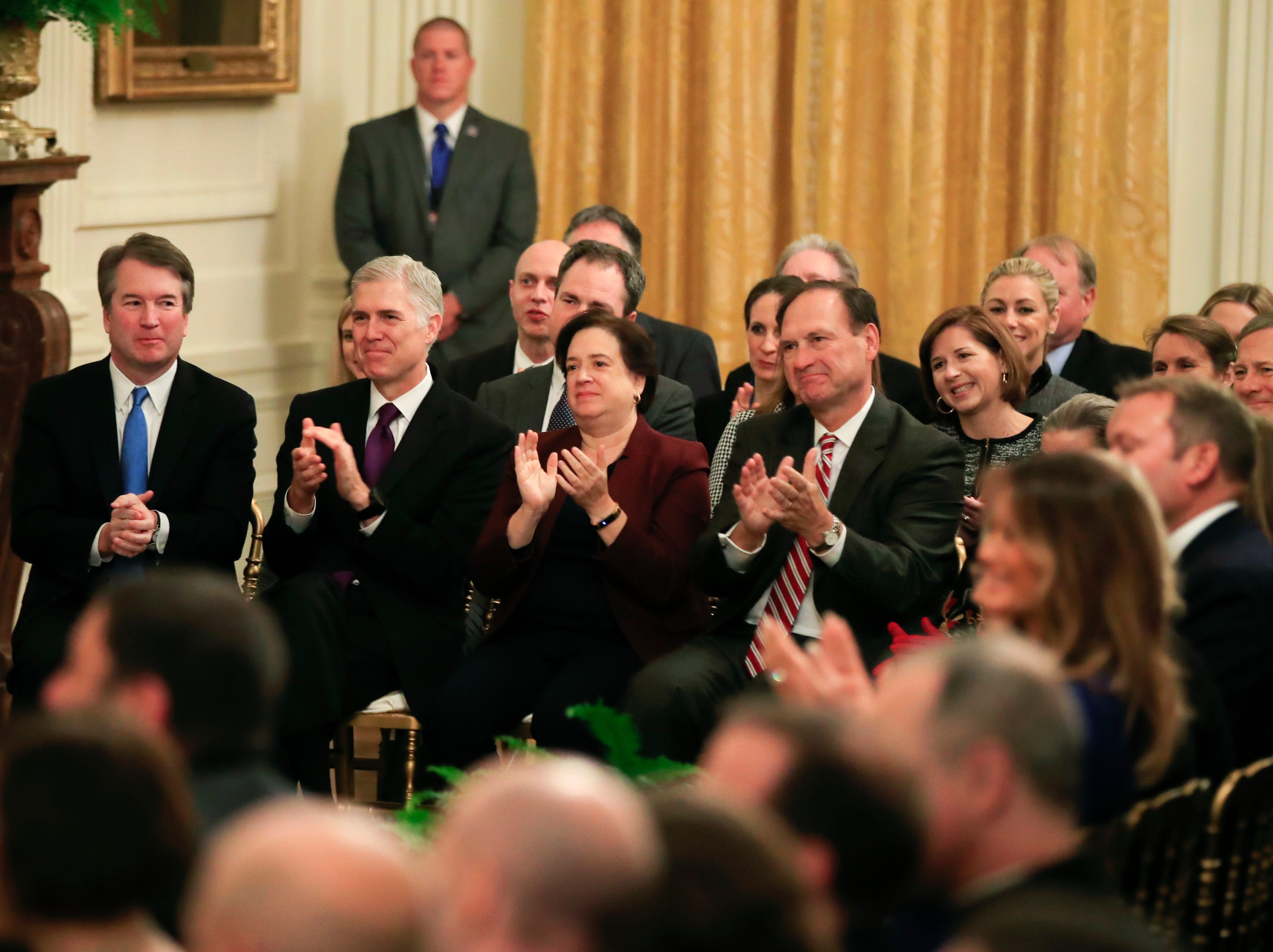 U.S. Supreme Court Justices, left to right, Brett Kavanaugh, Neil Gorsuch, Elena Kagan, Samuel Alito, Ruth Bader Ginsburg and Chief Justice John Roberts applaud as the late Justice Antonin Scalia is posthumously awarded by President Donald Trump the Presidential Medal of Freedom in the East Room of the White House, in Washington, D.C., on Friday, Nov. 16, 2018.