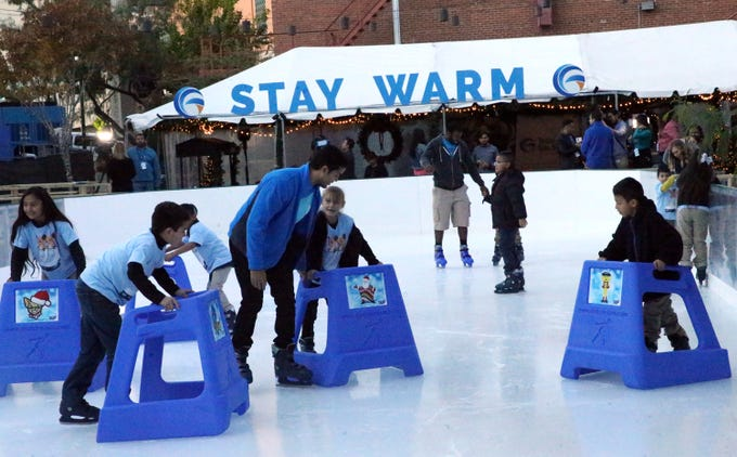 Kids from the Boys and Girls Clubs of El Paso get onto the ice with the help of supports that keep them balanced during a 'Break The Ice' kickoff event for WinterFest 2018 at Pioneer Plaza Friday in Downtown El Paso.