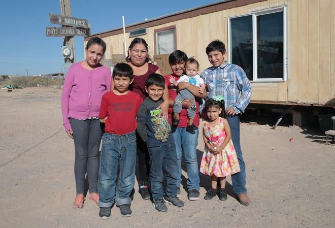 Norma Gonzalez, center, with her children Reyna Macias, 12, left, Edgar Macias, 8, Eswar Macias, 10, Martin Macias, 6, Emiliano Macias, 11, Lesli Macias, 2, and Jesus Macias, 5 months outside their Horizon City trailer.