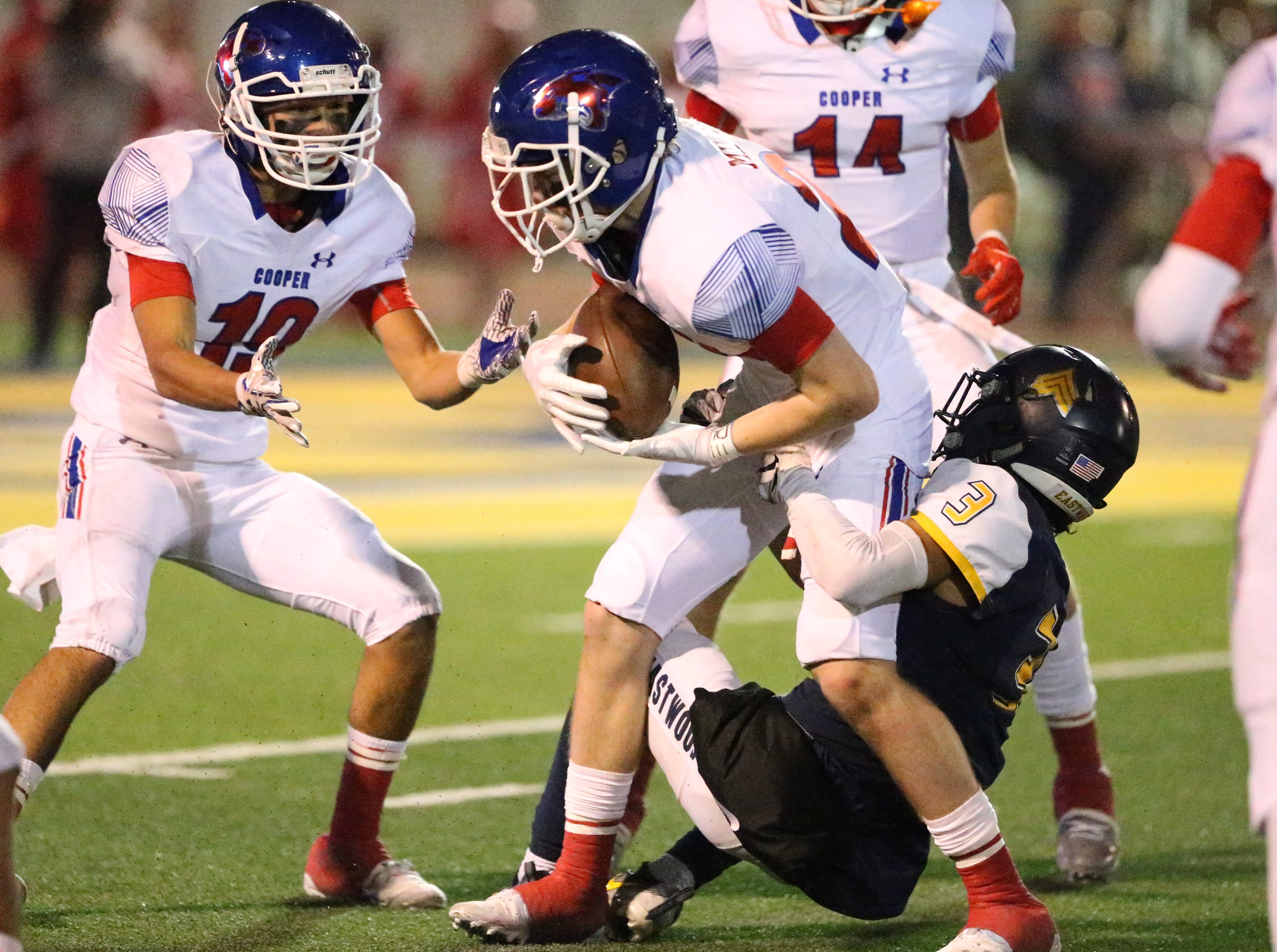 Brady Miller, center, Abilene Cooper prepared to lateral the ball to teammate Matthew Ramis, 10, before he is brought down by Eddie Cruz of Eastwood during a turnover Friday night.