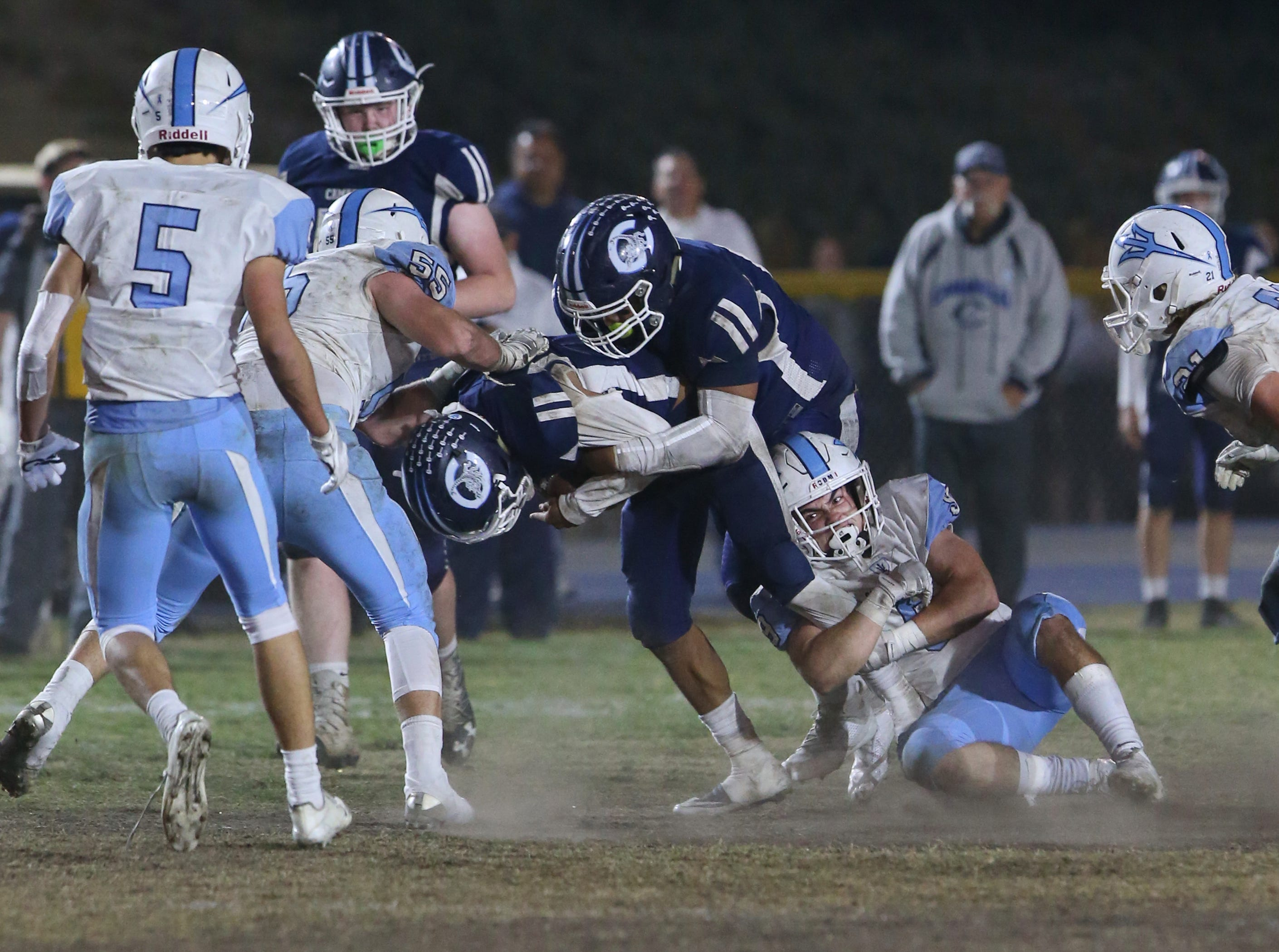 Corona del Mar's Luke Fisher holds onto Camarillo's Jesse Valenzuela leg as he makes the tackle during their CIF-SS Division 4 semifinal game Friday night.