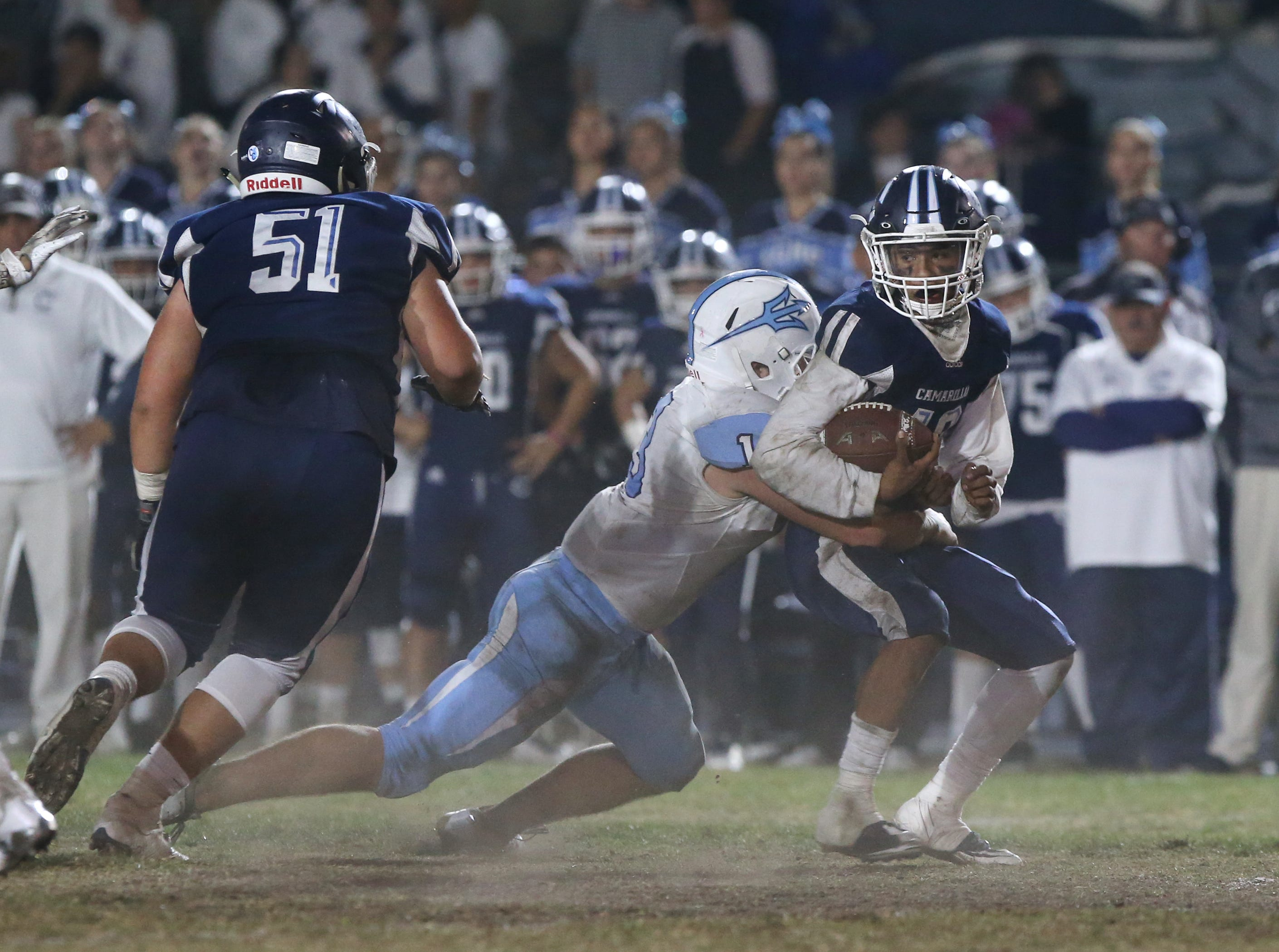 Camarillo High running back Jesse Valenzuela is stopped by Corona del Mar's Chase Zanck during their CIF-SS Division 4 semifinal game on Friday night.