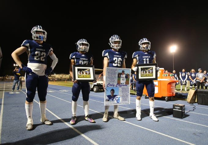 Camarillo High football players Carson Anderson, from left, Izaiah Lazaro, Drew Carter and Jack Holden and the entire team honored former player and school graduate Cody Gifford-Coffman, who was killed in last week's shooting at the Borderline Bar & Grill in Thousand Oaks, during an emotional ceremony before Friday night's playoff game against Corona del Mar. The Scorpions lost the Division 4 semifinal, 49-17.