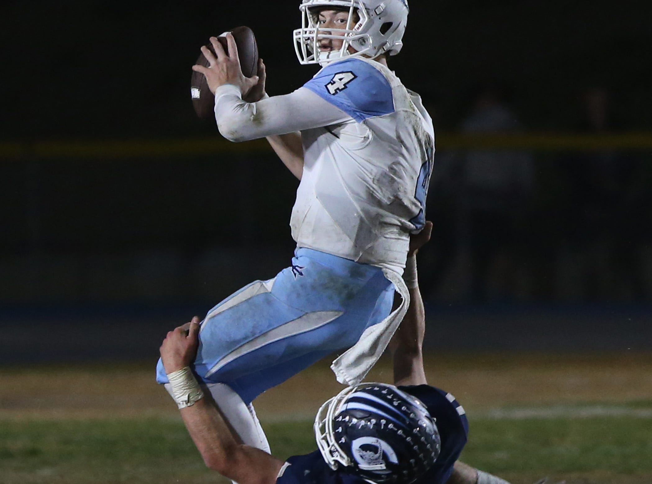 Camarillo High's Drew Carter pulls down Corona del Mar quarterback Ethan Garbers during Friday night's playoff game.
