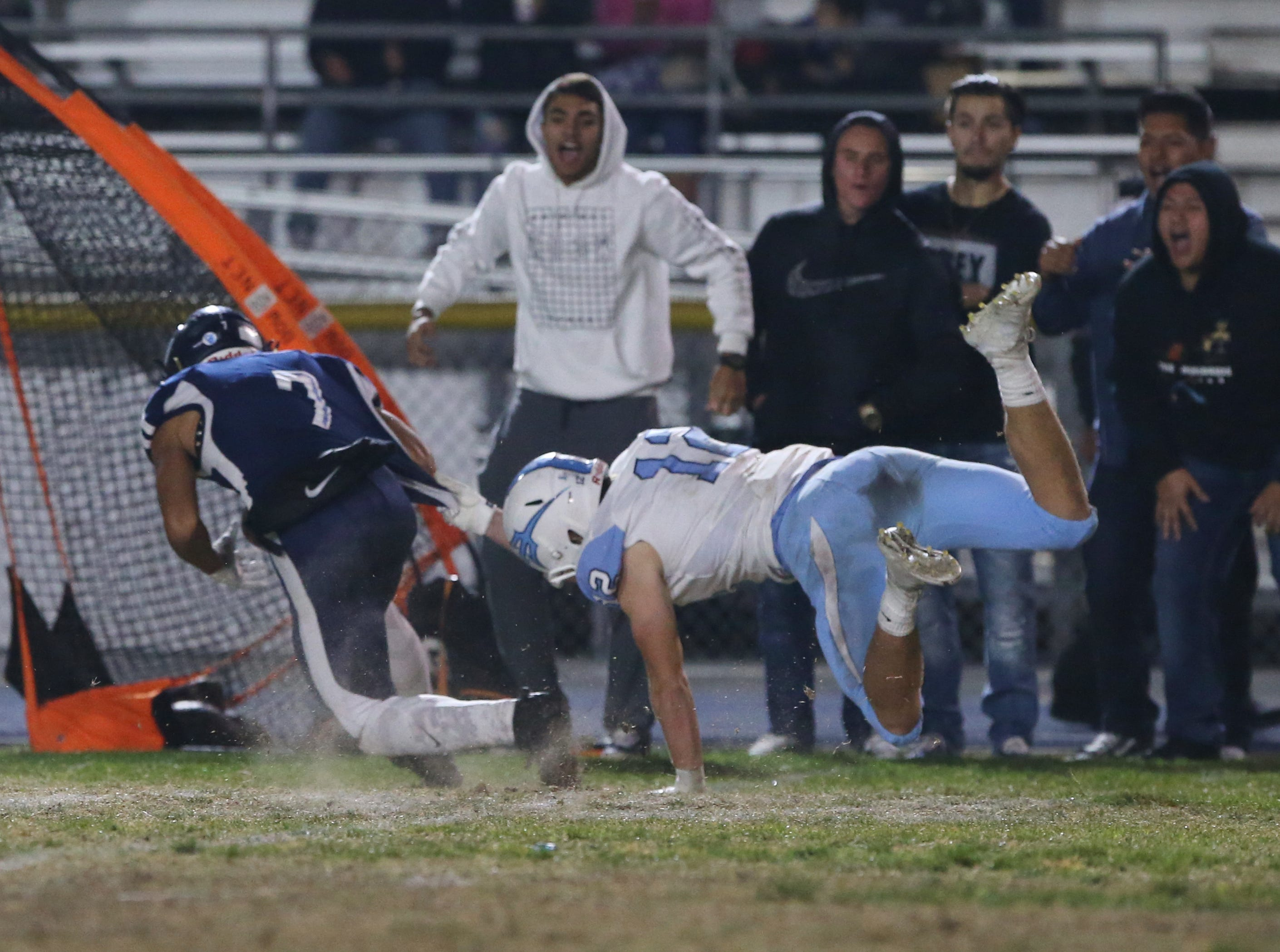 Camarillo High's Devin Norman, left, tries to escape the tackle attempt of Corona del Mar's Simon Hall during Friday night's playoff game.