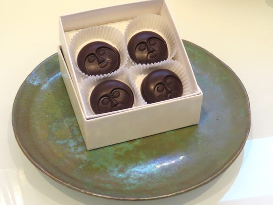A box of moon-face chocolates is displayed atop a lusterware plate by the late Ojai artist Beatrice Wood at the Beato Lounge inside The Porch Gallery in Ojai.