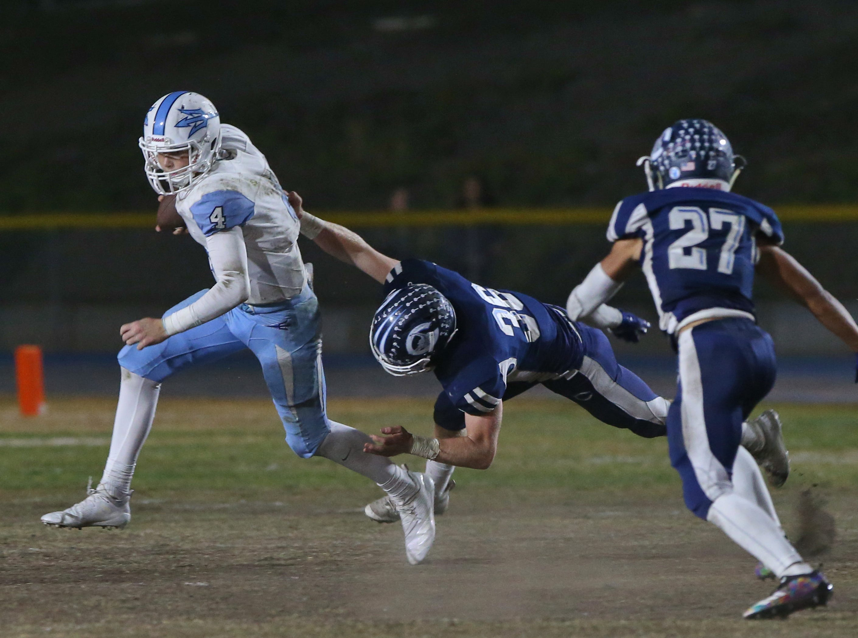 Camarillo High's Drew Carter tries to take down Corona del Mar quarterback Ethan Garbers during their CIF-SS Division 4 semifinal game on Friday.