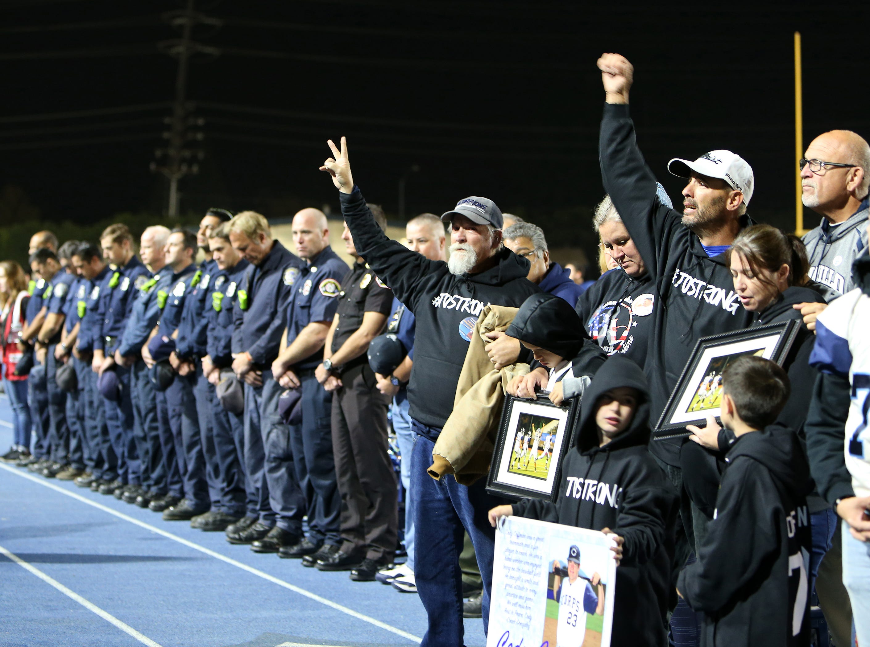 Cody Gifford-Coffman's grandfather Jerry Coffman, left, and his father Jason Coffman acknowledge the crowd before the start of Camarillo High's playoff game against Corona Del Mar on Friday night. The Ventura County Fire Department was also honored for its service fighting the fires that devastated Ventura County last week.