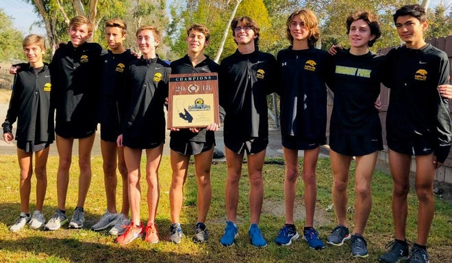 The Newbury Park High boys cross country team poses with its championship plaque after winning the Division 2 title at the CIF-Southern Section Finals on Saturday in Riverside.
