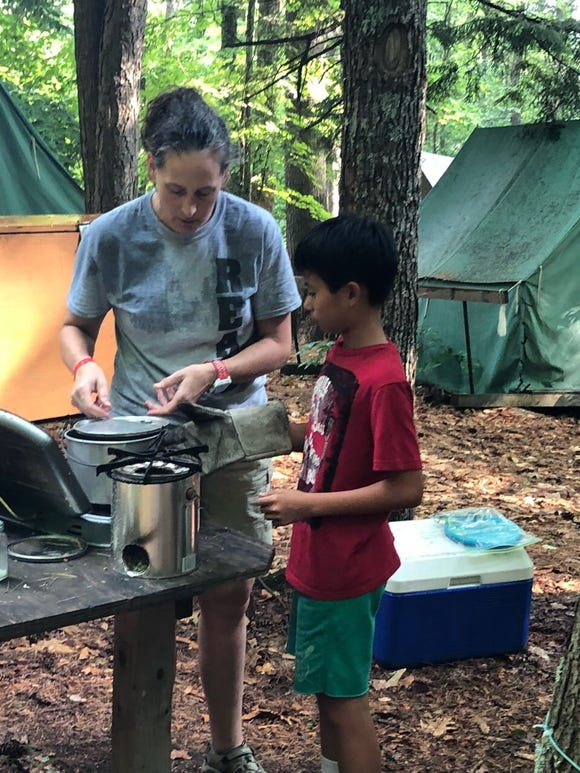 "Jann Mirchandani teaches a Scout how to cook on a ""hobo stove""at Camp Read in the Adirondacks this past summer."