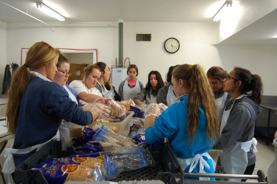 Members of the Vernon Horizon Club of Camp Fire assist with crumbling of bread to be used in the preparation of dressing for the 32nd annual Holiday Spirit Thanksgiving Meal Program. The free meal will be served Thanksgiving Day in the Empire Room of Wilbarger Memorial Auditorium. Meals will also be delivered to shut-ins.