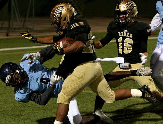 Rider's Tre Byrd (20) stiff arms his way through O.D. Wyatt's Gary Johnson (4) for a touchdown Friday, Nov. 16, 2018 at Memorial Stadium.
