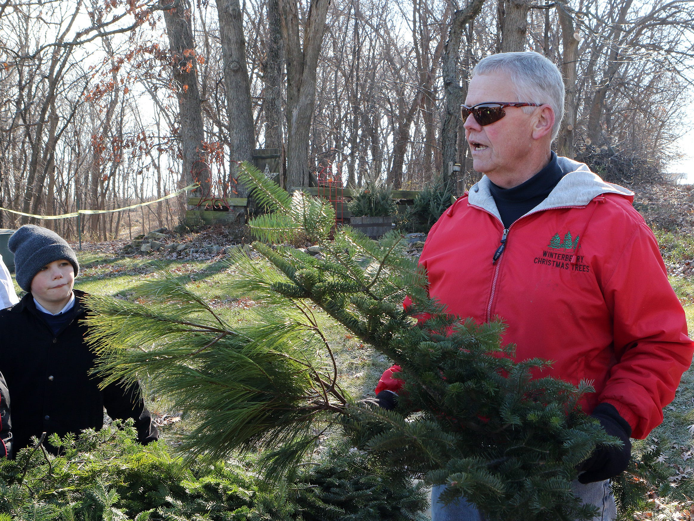 Greg Lancaster, owner of Lancaster's Winterberry Tree Farm in Brooklyn, teaches Albany fourth graders about Christmas trees during a visit on Nov. 15. Alice In Dairyland, Kaitlyn Riley, helped cut the first tree of the season.