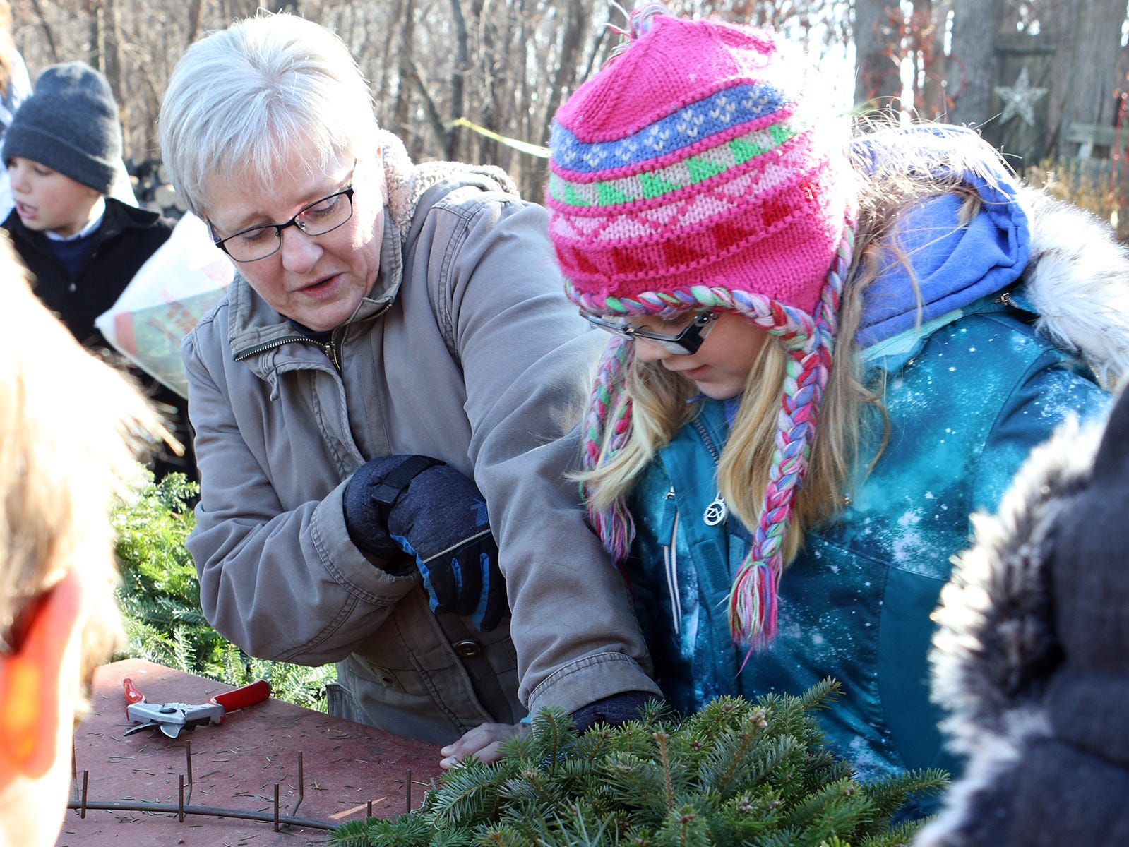 Vickie Lancaster gets help from an Albany fourth grade student in making a fresh wreath as students visited Lancaster's Winterberry Tree Farm on Nov. 15 to learn about the Christmas tree industry.