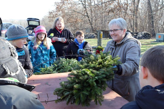 Vickie Lancaster shows students how a fresh wreath is made at Lancaster's Winterberry Tree Farm in Brooklyn on Nov. 15. Students learned about the Christmas tree industry and watched Alice in Dairyland help cut the first Christmas tree.