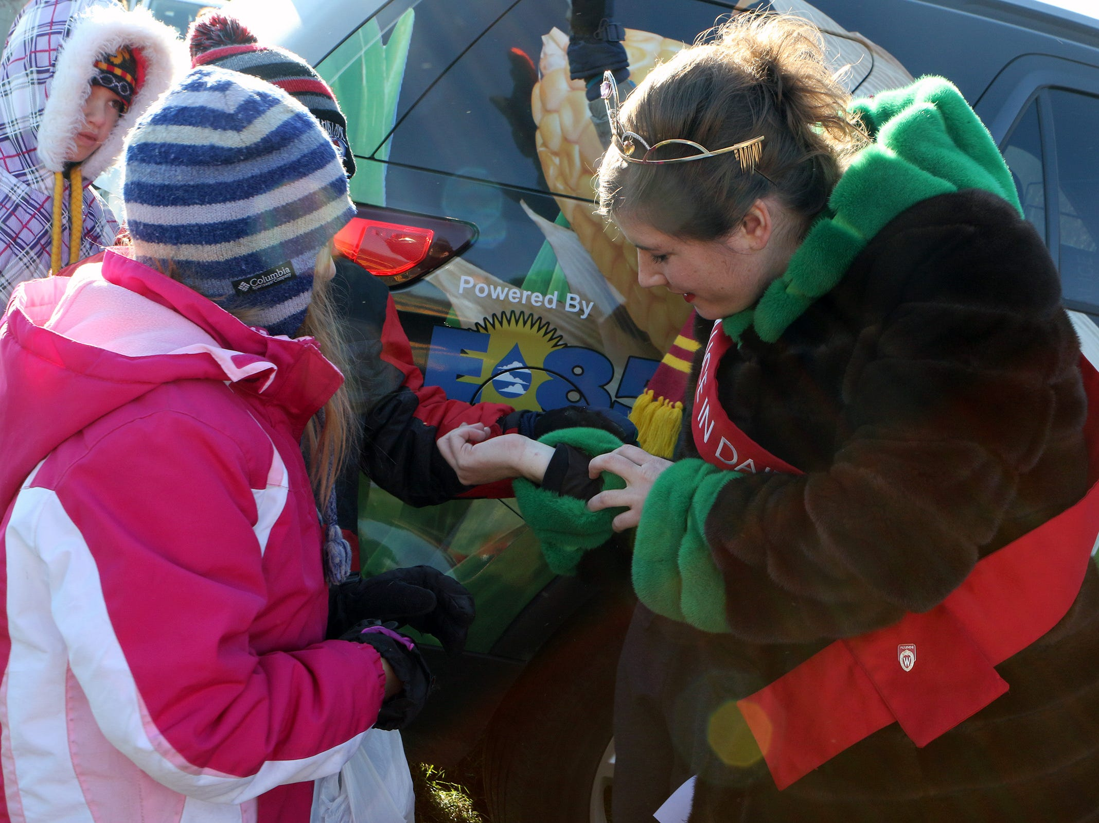 Alice in Dairyland, Kaitlyn Riley, shows New Glarus students the mink coat she got from the Wisconsin fur industry, a gift given to each Alice in Dairyland.