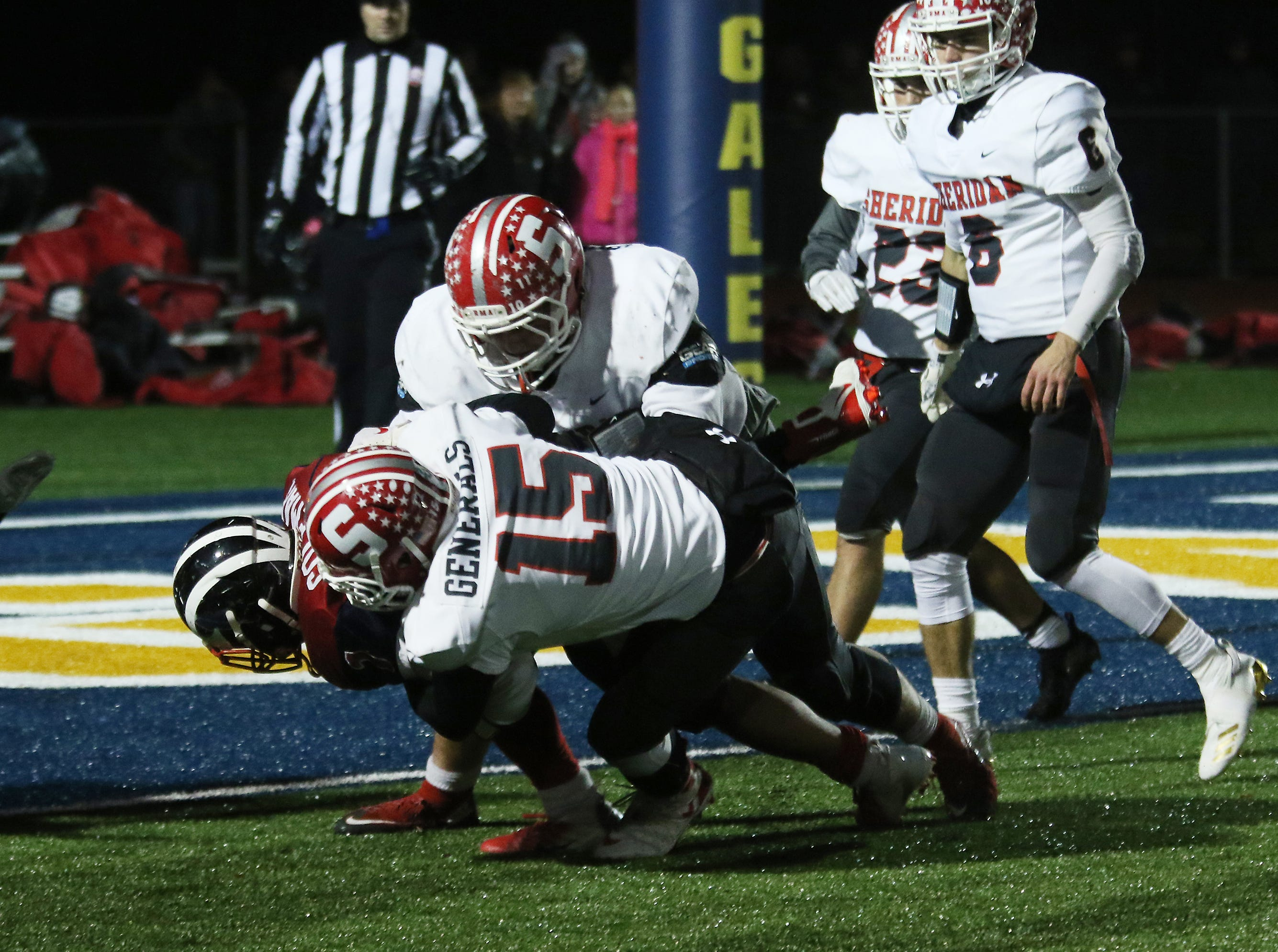 A pair of Sheridan defenders, including Alex Ogle (15) keep an Eastmoor ball carrier out of the endzone.