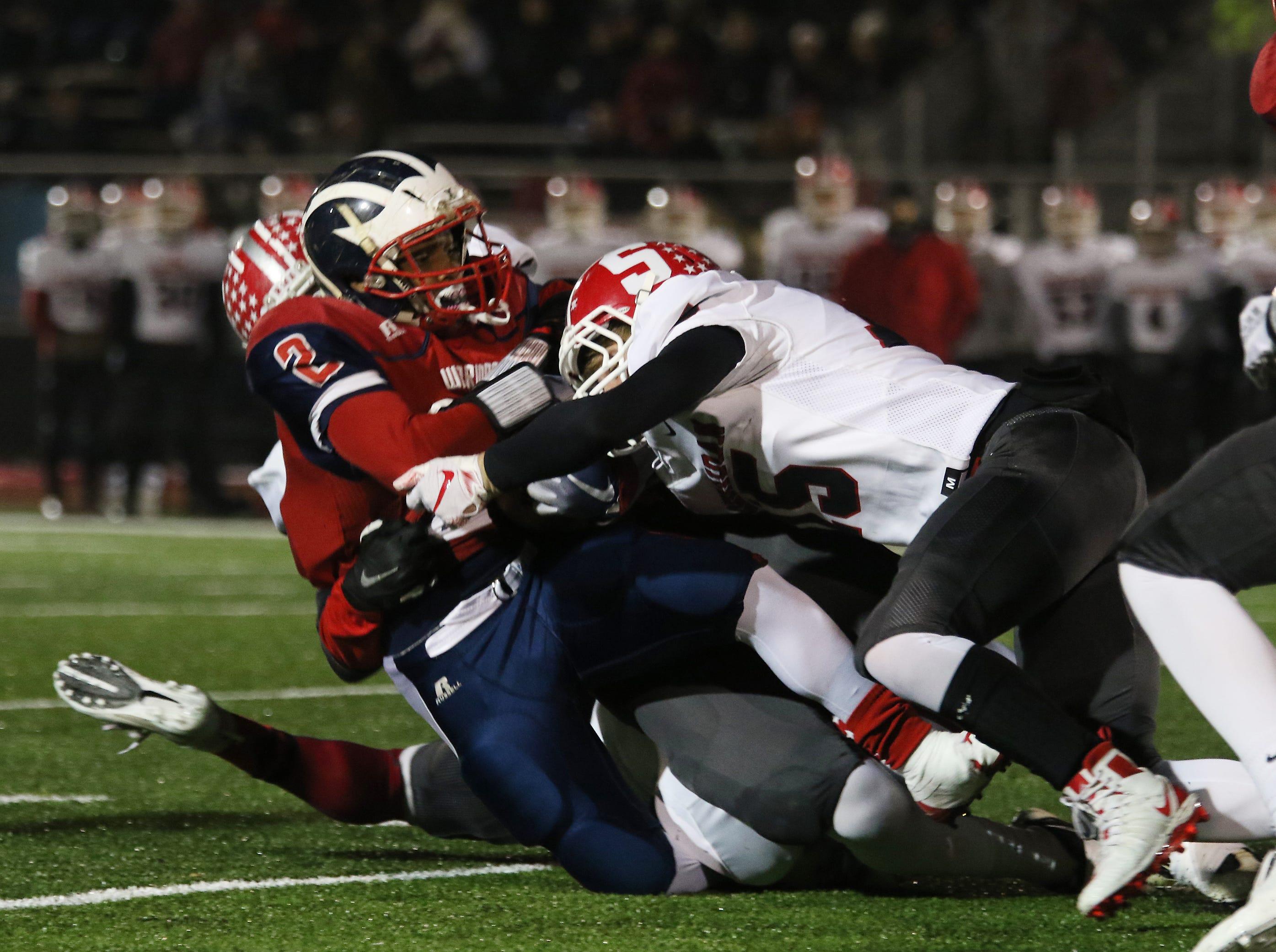 Sheridan defenders bring down an Eastmoor ball carrier.