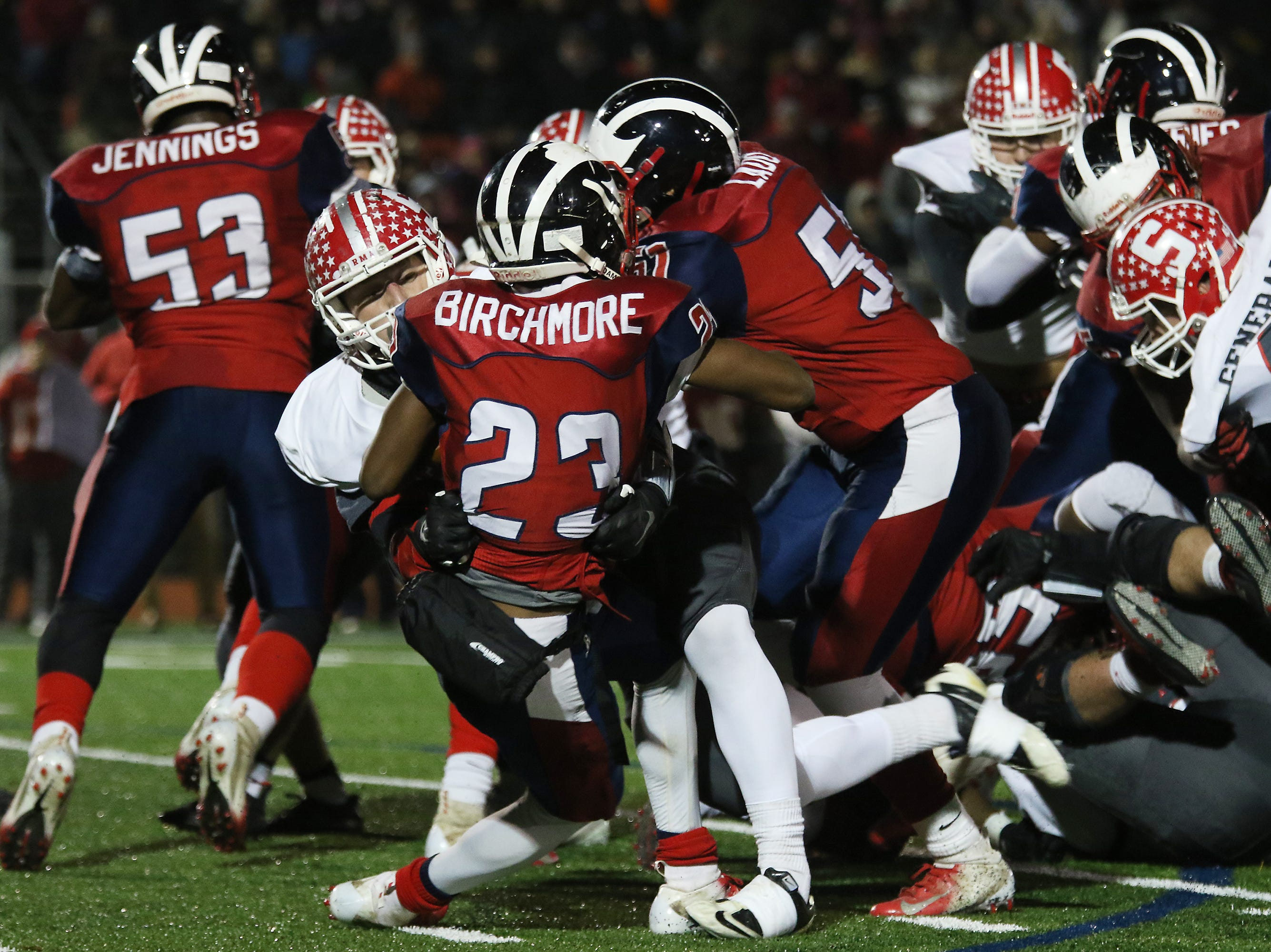 A Sheridan defender tackles an Eastmoor ball carrier.