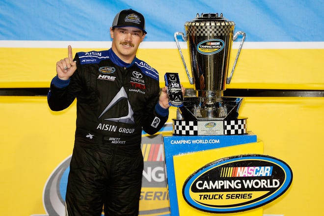 Brett Moffitt celebrates in victory lane with the trophy after winning the NASCAR Camping World Truck Series Ford EcoBoost 200 at Homestead-Miami Speedway.
