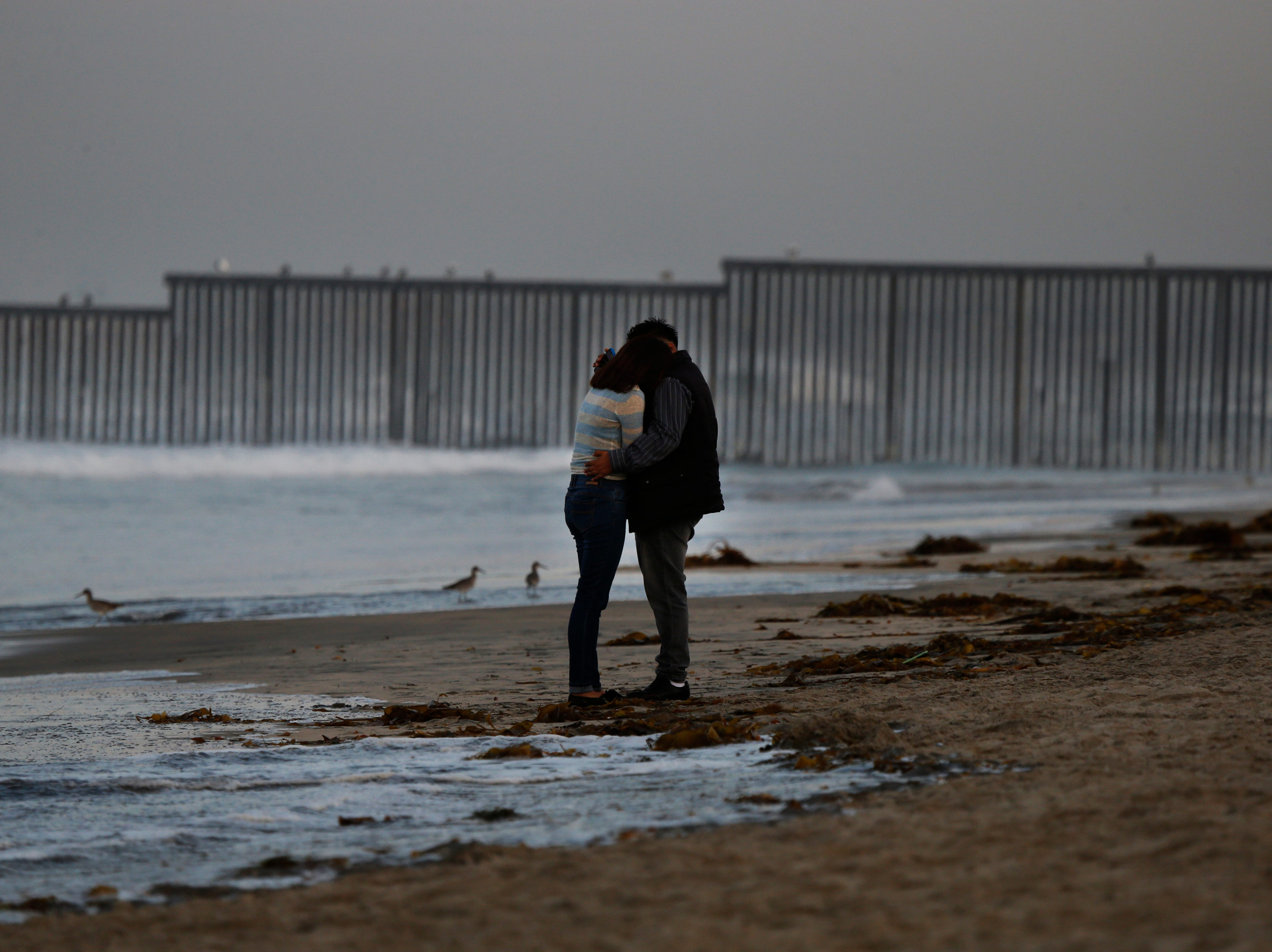 A couple embrace on the shore of Playa Tijuana backdropped by the barriers separating Mexico and the United States, where the border meets the Pacific Ocean, Saturday, Nov. 17, 2018.