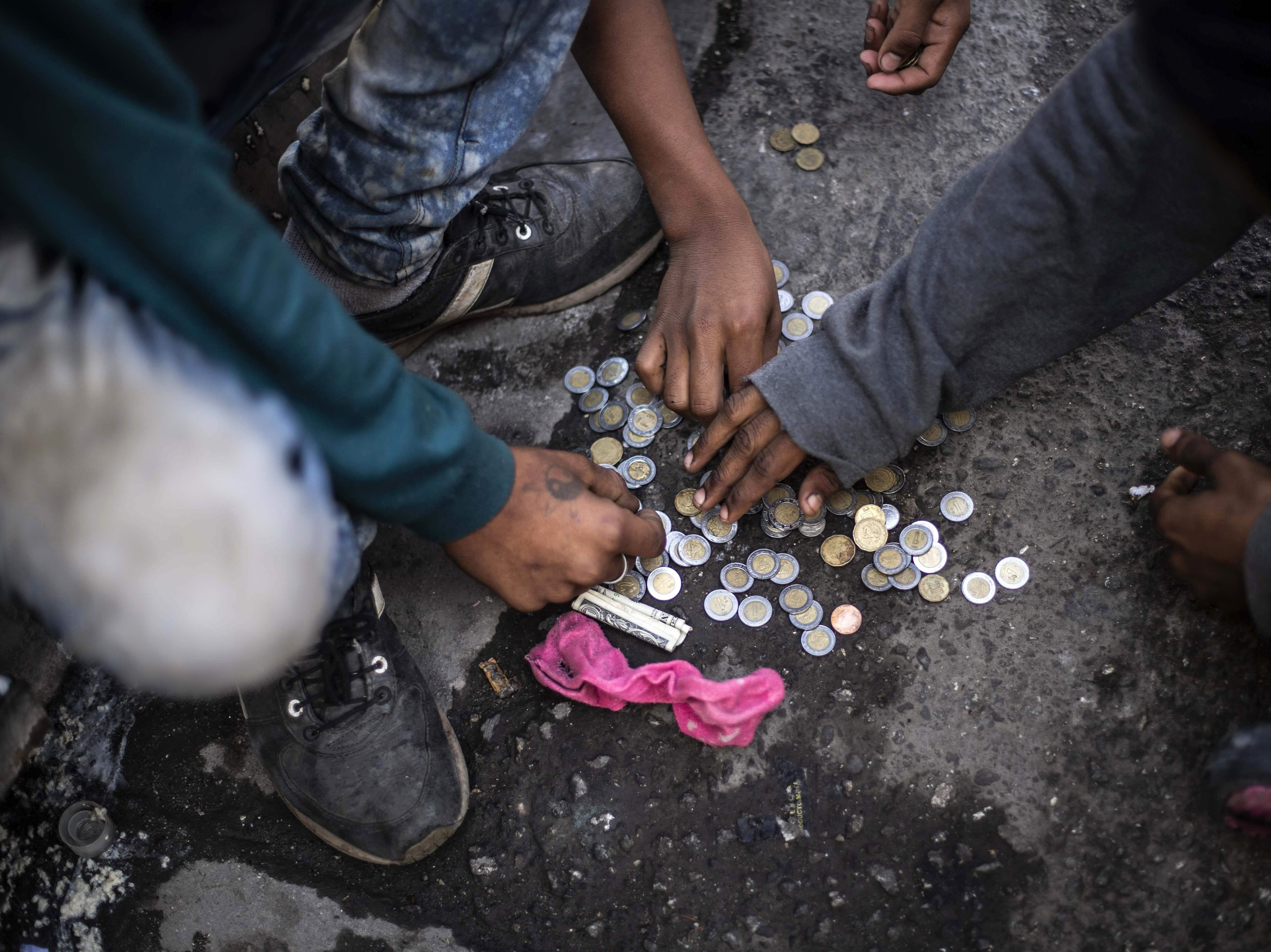Central American migrants moving towards the United States in hopes of a better life, count coins at the Alfa y Omega shelter, in Mexicali, Baja California state, Mexico, on Nov. 17, 2018.