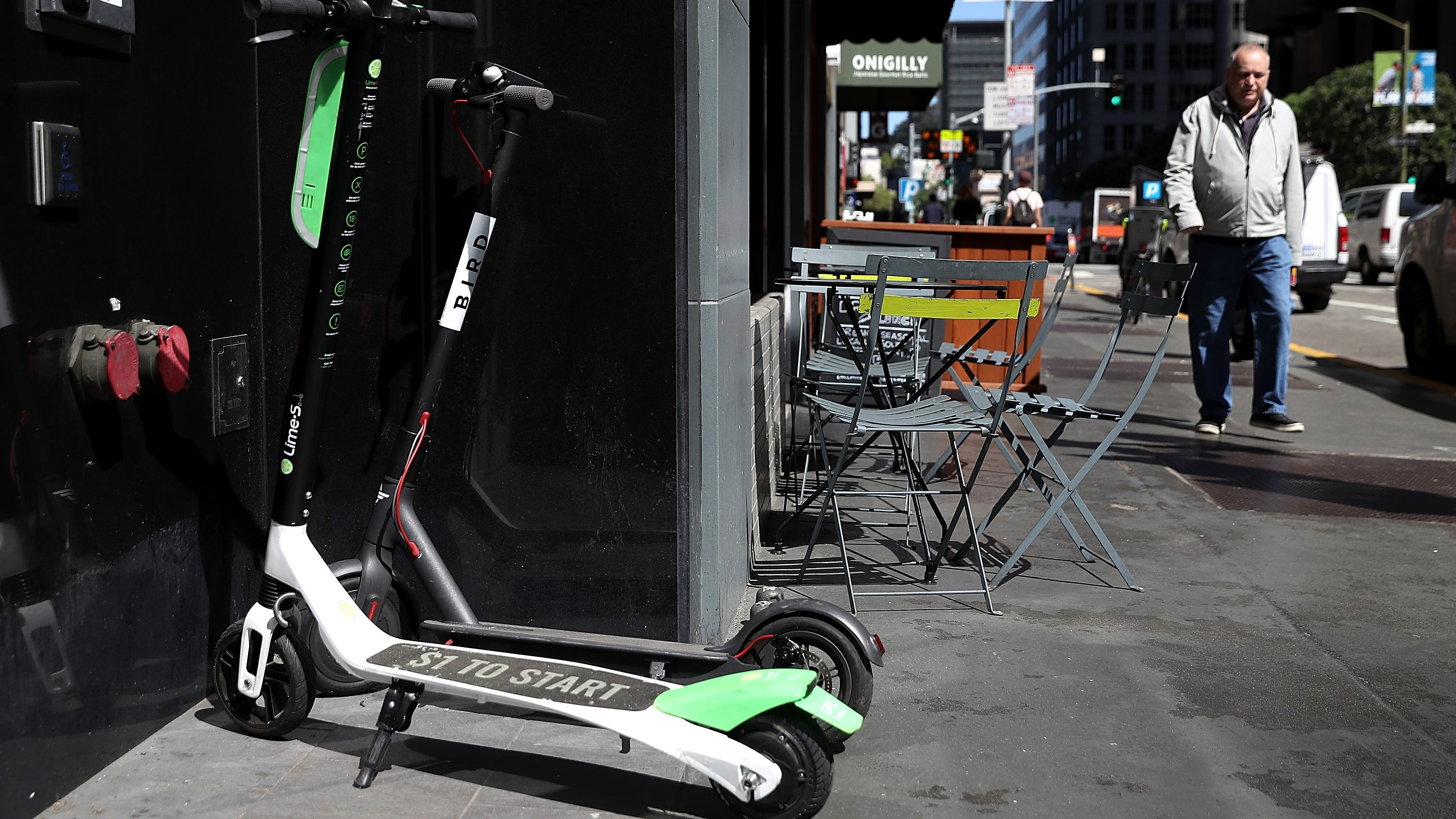Bird and Lime scooters sit parked in front of a building on April 17, 2018, in San Francisco.