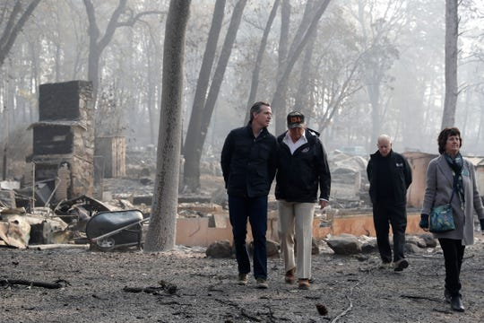 President Donald Trump talks tours a destroyed neighborhood with from left, Gov.-elect Gavin Newsom, California Gov. Jerry Brown and Paradise Mayor Jody Jones during a visit to areas impacted by the wildfires, Saturday, Nov. 17, 2018, in Paradise Calif.