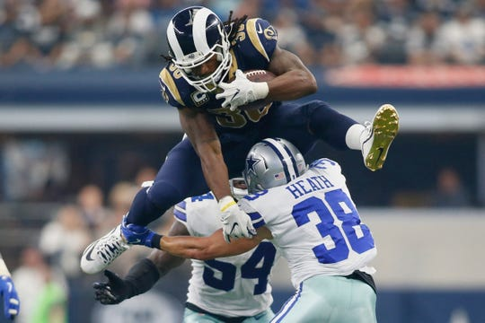 Rams running back Todd Gurley (30) tries to hurdle Dallas safety Jeff Heath (38) in a 2017 game.