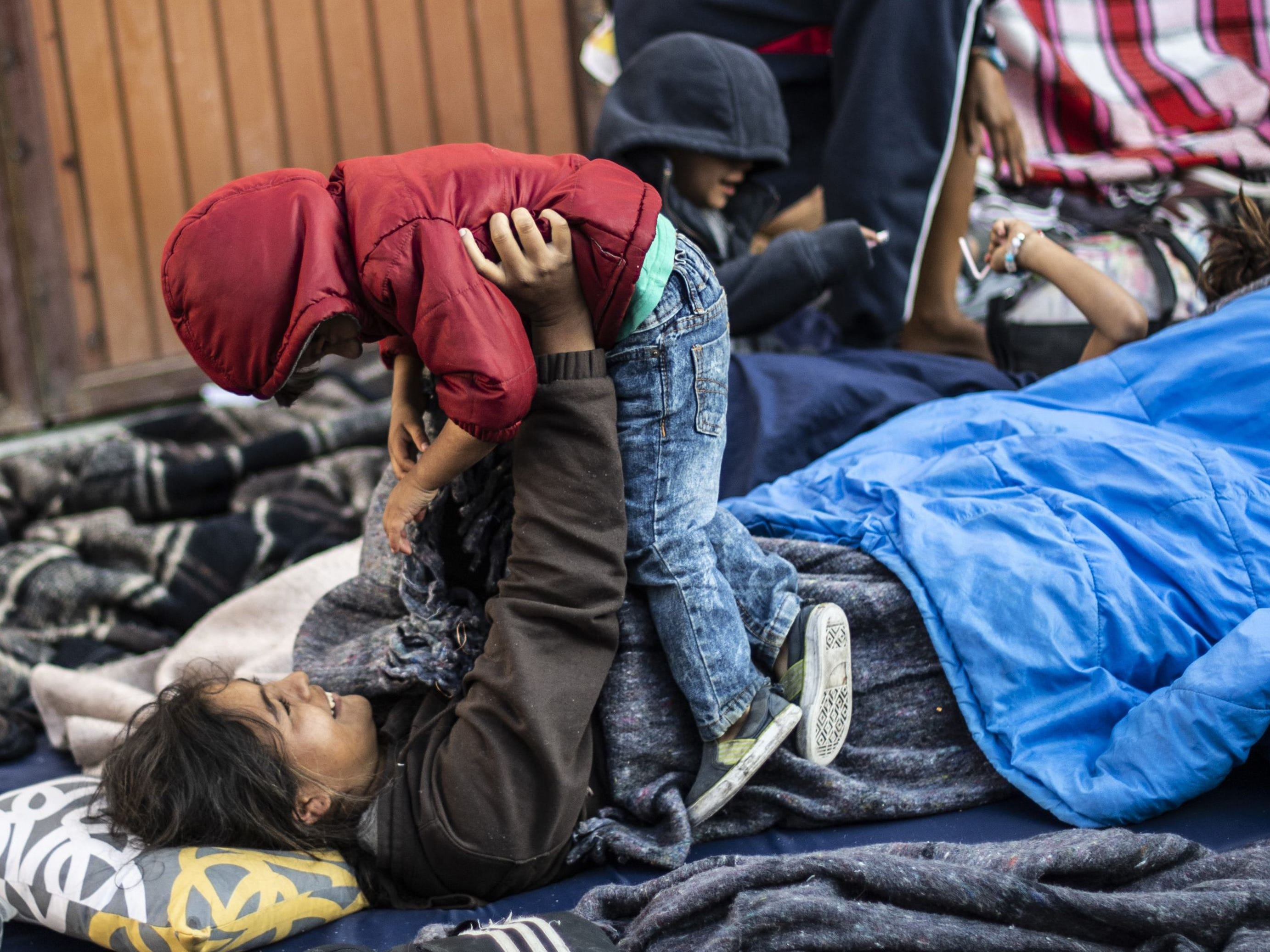 A Central American migrant woman moving towards the United States in hopes of a better life, plays with a child at the Alfa y Omega shelter in Mexicali, Baja California state, Mexico, on Nov. 17, 2018.