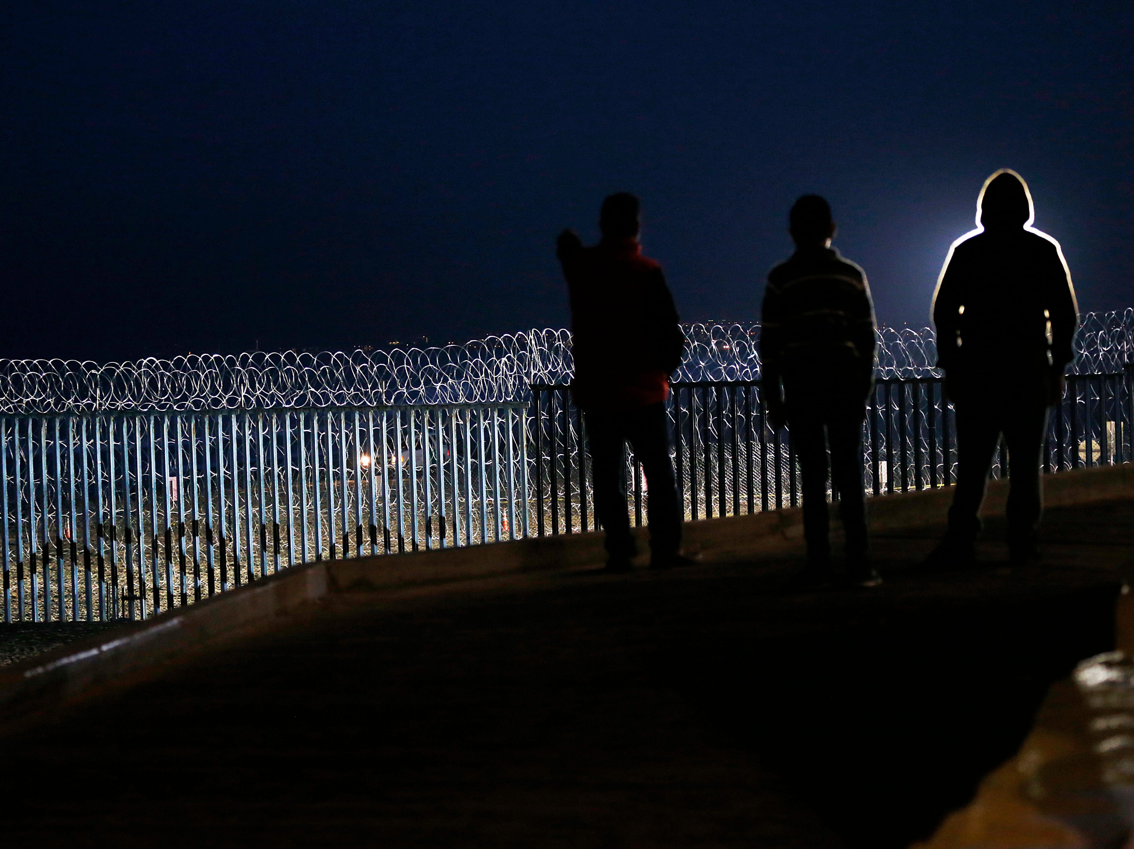 "Residents stand on a hill before barriers, wrapped in concertina wire, separating Mexico and the United States, where the border meets the Pacific Ocean, in Tijuana, Mexico, Saturday, Nov. 17, 2018. Many of the nearly 3,000 migrants have reached the border with California. The mayor has called the migrants' arrival an ""avalanche"" that the city is ill-prepared to handle."