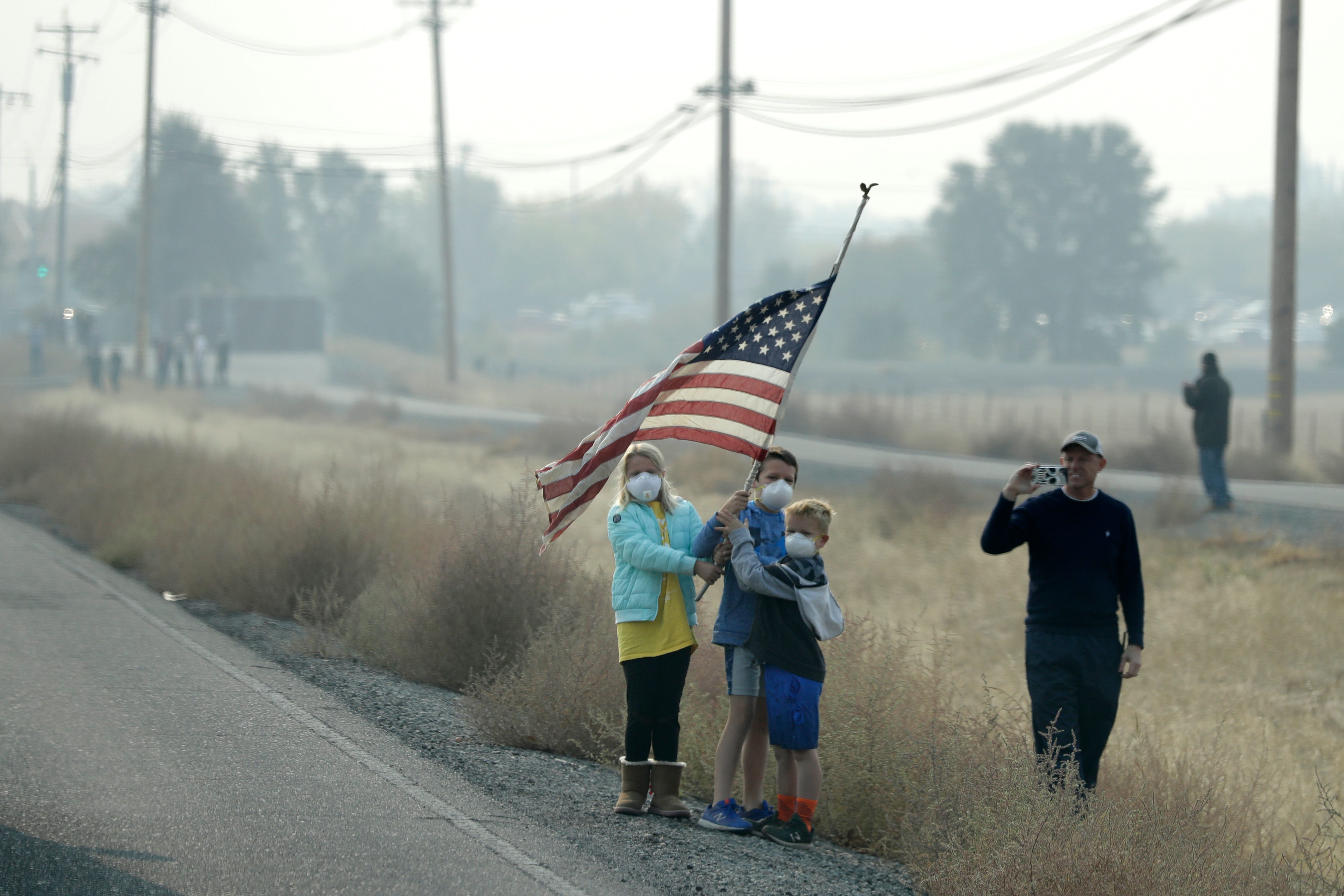 People stand on the side of the road holding an American flag as the motorcade of President Donald Trump drives through Chico, Calif., on a visit to areas affected by the wildfires, Saturday, Nov. 17, 2018.
