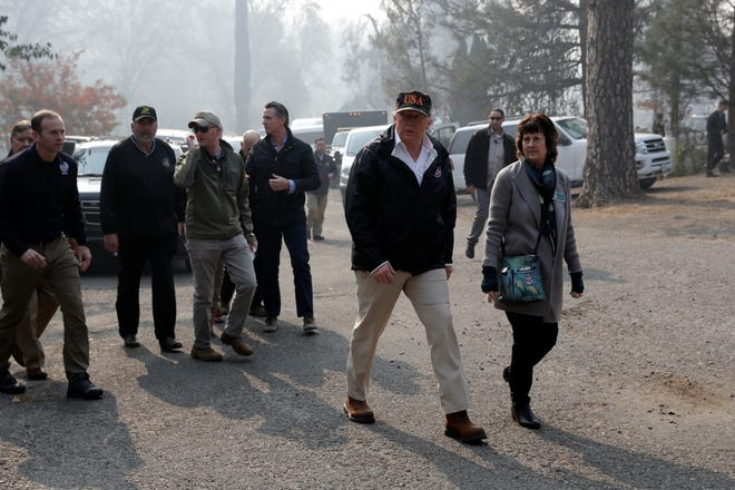President Donald Trump walks with Mayor Jody Jones as he visits a neighborhood impacted by the wildfires, Saturday, Nov. 17, 2018, in Paradise, Calif.