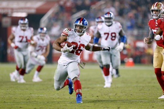 New York Giants running back Saquon Barkley (26) runs with the ball after making a catch against the San Francisco 49ers in the fourth quarter at Levi's Stadium.