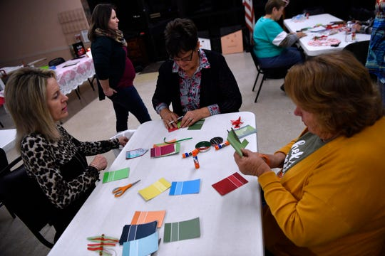 Angie Halfmann (left), Sharon Engler and Sandra Rollwitz make gift tags using hardware store paint chips Wednesday.
