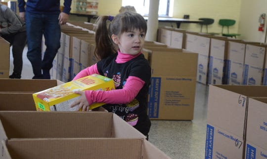 Duchess Gillem, 4, makes sure before putting a box of cereal in a box for Thanksgiving meals.
