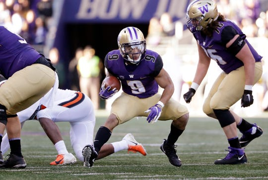 Washington's Myles Gaskin (9) cuts back on a first-half run.