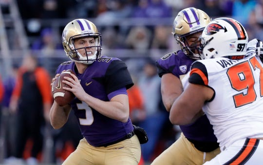 Washington quarterback Jake Browning (left) drops back to pass against Oregon State in the first half.
