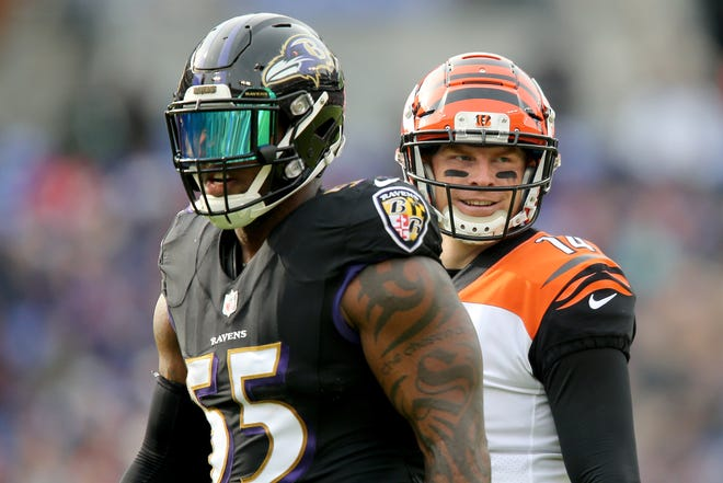 Cincinnati Bengals quarterback Andy Dalton (14) smiles back to the bench after exchanging words with Baltimore Ravens outside linebacker Terrell Suggs (55) in the second quarter of an NFL football game, Sunday, Nov. 18, 2018, at M&T Bank Stadium in Baltimore.