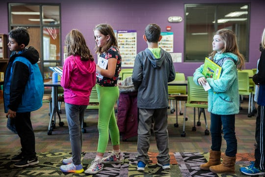 Third-grade students at Rock Creek Elementary wait in line to check out books in the school's library.