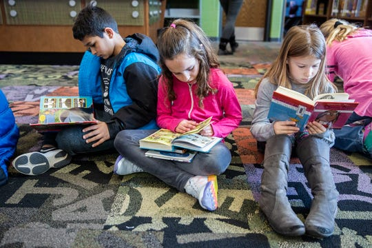 Third grade students at Rock Creek Elementary read books after checking them out in the school's library on Wednesday, Nov. 14, 2018, in Ankney.