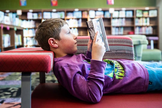Parker Gunn, a third-grade student at Rock Creek Elementary, reads a book in the school's library.