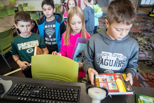 Third-grade students at Ankeny's Rock Creek Elementary check out books in the school's library on Nov. 14.