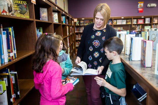 Corissa Thompson, the district-level K-5 librarian in Ankeny, helps third-grade students at Rock Creek Elementary pick out a book on Nov. 14.
