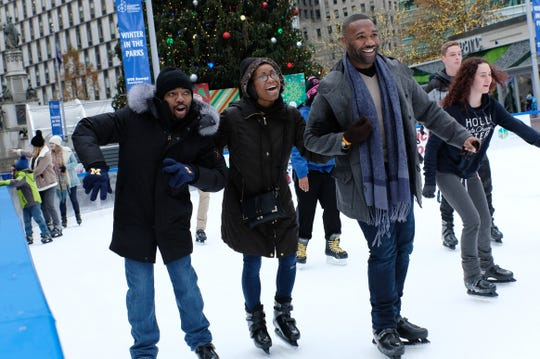 From left, Waymon Peer, Bri'An Davis and Azar Alexander, all of Detroit, share a laugh as they skate with linked arms during opening weekend for the ice rink at Campus Martius Park in downtown Detroit on Sunday, November 18, 2018.